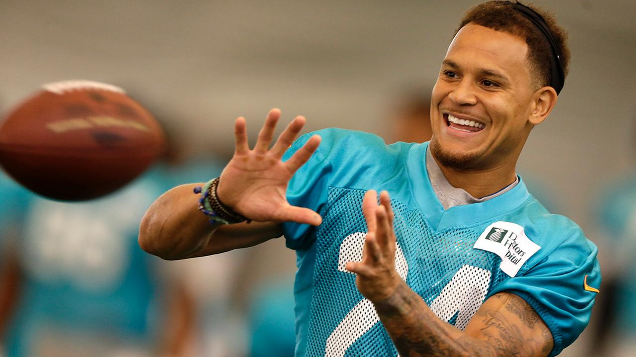 Cornerback Cortland Finnegan (24) smiles as he prepares to catch a pass during NFL football training camp in Davie, Fla., Monday,Aug. 4, 2014.