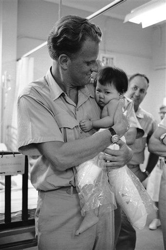 <div class='meta'><div class='origin-logo' data-origin='AP'></div><span class='caption-text' data-credit=''>Evangelist Billy Graham holds a small Vietnamese Girl, who is having her legs treated, during a visit to the U.S. 3rd field hospital in Saigon Dec. 21, 1966.</span></div>