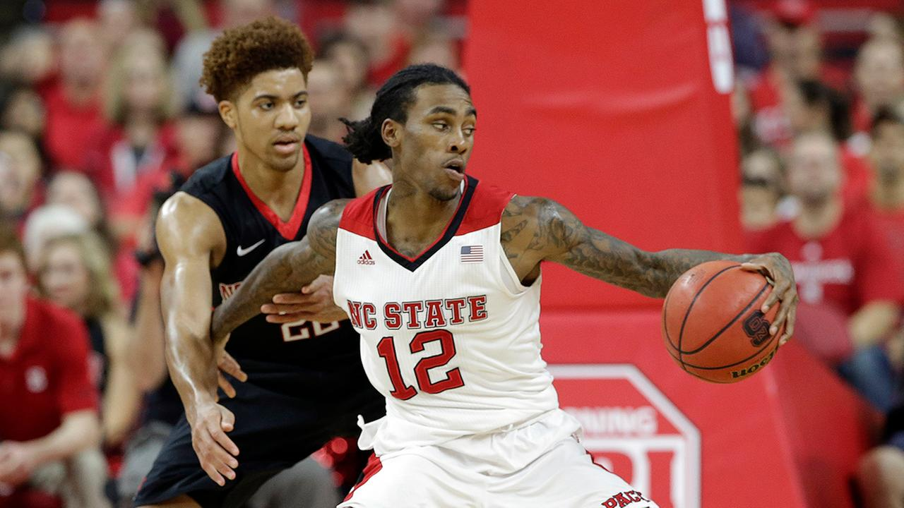 NC States Anthony Barber (12) is pressured by Northeasterns Donnell Gresham Jr.  on Dec. 29,, 2015. Barber finished with 29 points.