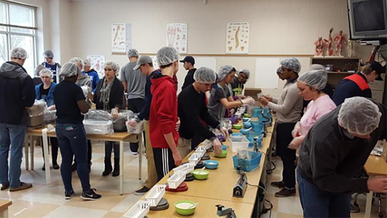 High school students pack 12,000 meals for charity
