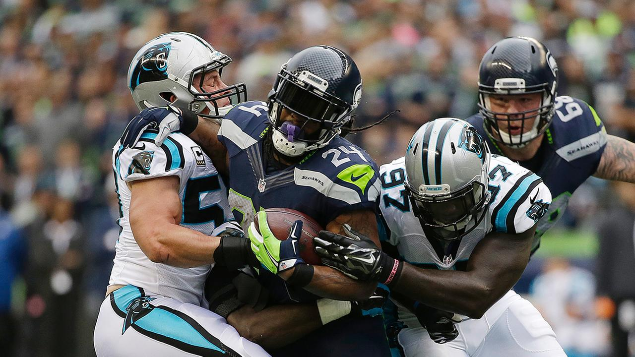 Seattle Seahawks running back Marshawn Lynch (24) runs between Carolina Panthers Luke Kuechly, left, and Mario Addison (97) on Oct. 18.
