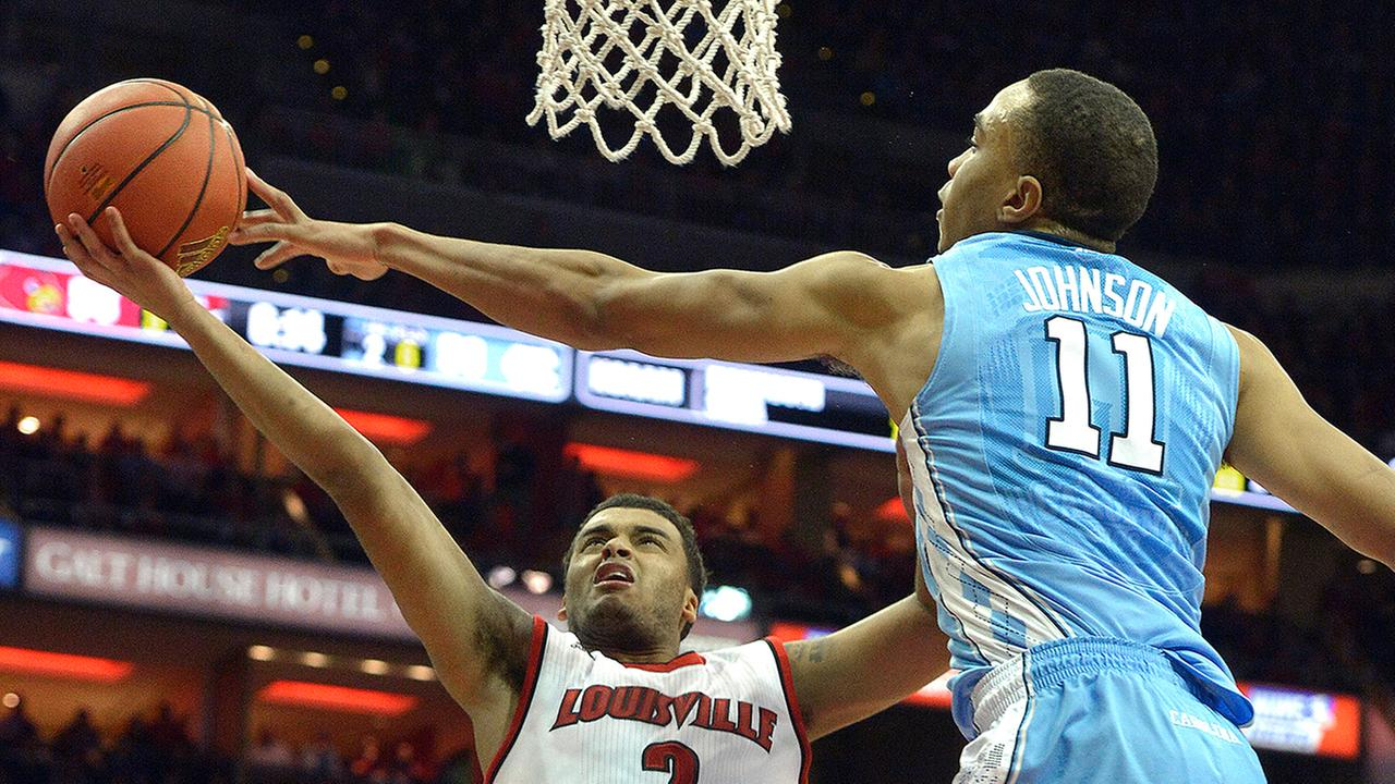 North Carolinas Brice Johnson (11) defends against Louisvilles Quentin Snider (2) on Monday night.
