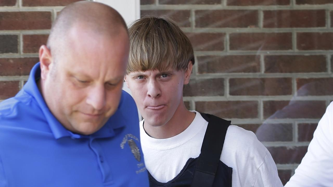 In this June 18, 2015 file photo, Charleston, S.C., shooting suspect Dylann Storm Roof, center, is escorted from the Shelby Police Department in Shelby, N.C.