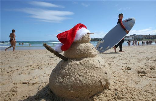 "<div class=""meta image-caption""><div class=""origin-logo origin-image none""><span>none</span></div><span class=""caption-text"">A young surfer walks past a snowman made of sand while celebrating Christmas Day on Bondi Brach in Sydney, Australia. (AP Photo/ Rick Rycroft)</span></div>"