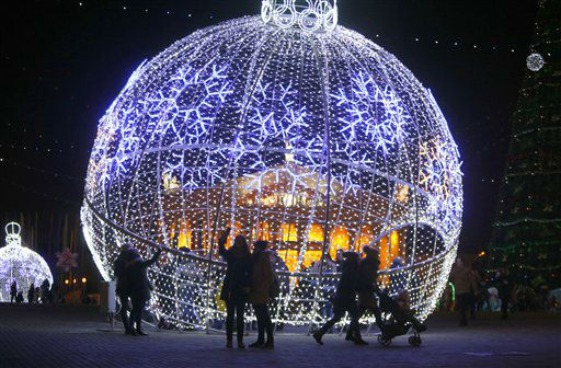 """<div class=""""meta image-caption""""><div class=""""origin-logo origin-image none""""><span>none</span></div><span class=""""caption-text"""">People walk next to a giant Christmas ball installed in Octyabrskaya Square and decorated to mark the  Christmas and New Year celebrations in Minsk, Belarus.  (AP Photo/ Sergei Grits)</span></div>"""