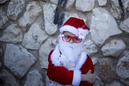 """<div class=""""meta image-caption""""><div class=""""origin-logo origin-image none""""><span>none</span></div><span class=""""caption-text"""">An Israeli Arab Christian boy dressed up as Santa Claus waits for the start of the annual Christmas parade in in the northern Israeli city of Nazareth, Israel.  (AP Photo/ Ariel Schalit)</span></div>"""