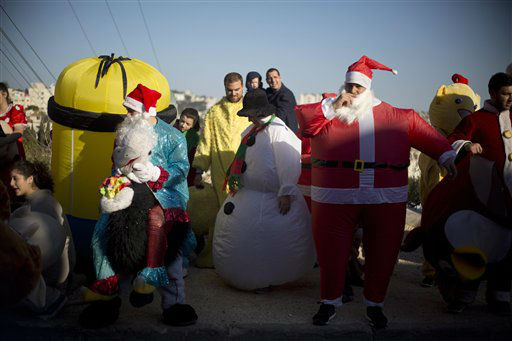 """<div class=""""meta image-caption""""><div class=""""origin-logo origin-image none""""><span>none</span></div><span class=""""caption-text"""">Israeli Arab Christians, one dressed up as Santa Claus, wait for the start of the annual Christmas parade in in the northern Israeli city of Nazareth, Israel.  (AP Photo/ Ariel Schalit)</span></div>"""