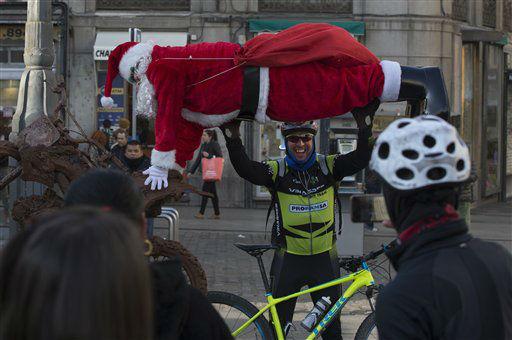 "<div class=""meta image-caption""><div class=""origin-logo origin-image none""><span>none</span></div><span class=""caption-text"">A man poses for a photo beneath a human statue dressed as Santa Claus in Madrid, Spain.  (AP Photo/ Paul White)</span></div>"