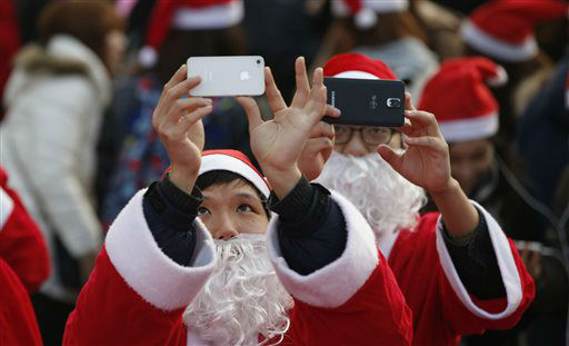 """<div class=""""meta image-caption""""><div class=""""origin-logo origin-image none""""><span>none</span></div><span class=""""caption-text"""">Volunteers clad in Santa Claus costumes takes photos during a Christmas charity event as they gather to deliver gifts for the poor in downtown Seoul, South Korea.  (AP Photo/ Lee Jin-man)</span></div>"""