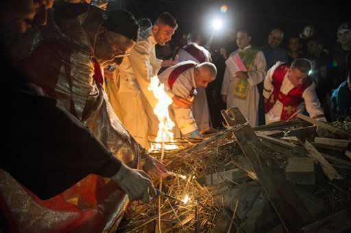 """<div class=""""meta image-caption""""><div class=""""origin-logo origin-image none""""><span>none</span></div><span class=""""caption-text"""">Assiryan-Catholic Archbishop of Mosul, Youhanna Boutros Moshe lights the holy fire during mass in the Al-Bashara Church in a Christian refugee camp in Irbil, northern Iraq.   (AP Photo/ Seivan M. Salim)</span></div>"""