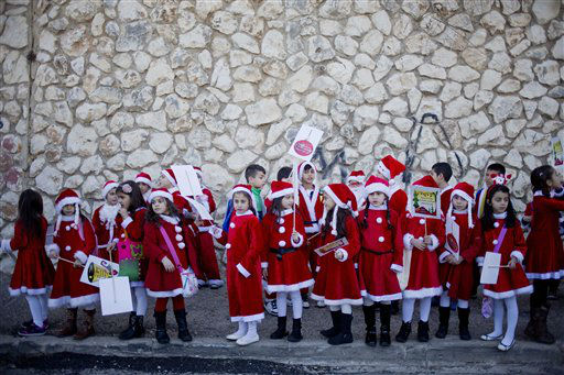 """<div class=""""meta image-caption""""><div class=""""origin-logo origin-image none""""><span>none</span></div><span class=""""caption-text"""">Israeli Arab Christians dressed up as Santa Claus wait for the start of the annual Christmas parade in in the northern Israeli city of Nazareth, Israel.  (AP Photo/ Ariel Schalit)</span></div>"""