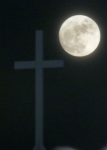 """<div class=""""meta image-caption""""><div class=""""origin-logo origin-image none""""><span>none</span></div><span class=""""caption-text"""">The Long Night Moon rises behind a cross at Christ Community Church in Lawrence, Kan.  (AP Photo/ Orlin Wagner)</span></div>"""