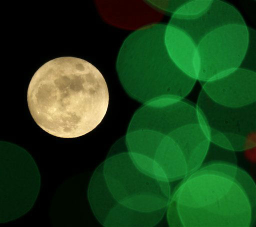 """<div class=""""meta image-caption""""><div class=""""origin-logo origin-image none""""><span>none</span></div><span class=""""caption-text"""">The nearly full moon is seen among Christmas lights at a holiday display in Lenexa, Kan. (AP Photo/ Charlie Riedel)</span></div>"""