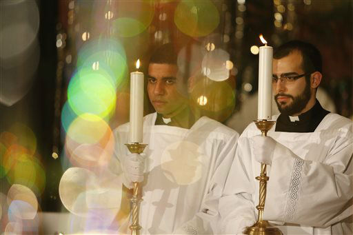 """<div class=""""meta image-caption""""><div class=""""origin-logo origin-image none""""><span>none</span></div><span class=""""caption-text"""">Catholic priests hold candle during Christmas midnight Mass in Sarajevo's Cathedral, Bosnia. (AP Photo/ Amel Emric)</span></div>"""