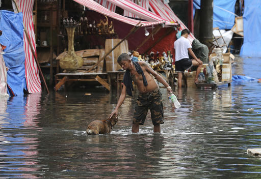 "<div class=""meta image-caption""><div class=""origin-logo origin-image none""><span>none</span></div><span class=""caption-text"">A man pets a dog along a flooded street caused by rains from Typhoon Nock-Ten in Quezon city, north of Manila (AP Photo/Aaron Favila)</span></div>"
