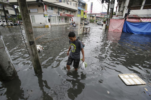 "<div class=""meta image-caption""><div class=""origin-logo origin-image none""><span>none</span></div><span class=""caption-text"">A man wades along a flooded street caused by rains from Typhoon Nock-Ten in Quezon city, north of Manila. (AP Photo/Aaron Favila)</span></div>"