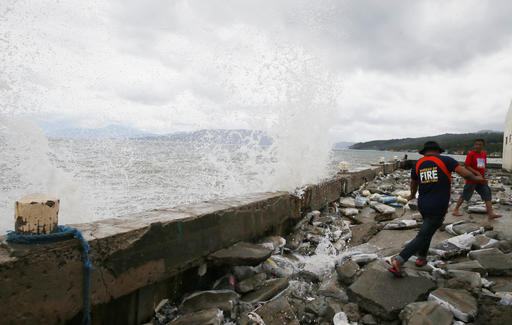 "<div class=""meta image-caption""><div class=""origin-logo origin-image none""><span>none</span></div><span class=""caption-text"">A fireman and a resident avoid the waves which was brought by typhoon Nock-Ten. (AP Photo/Bullit Marquez)</span></div>"
