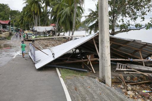 "<div class=""meta image-caption""><div class=""origin-logo origin-image none""><span>none</span></div><span class=""caption-text"">The entire roof of a store partially blocks the road after being swept by typhoon Nock-Ten, at Mabini township, Batangas province south of Manila.(AP Photo/Bullit Marquez)</span></div>"