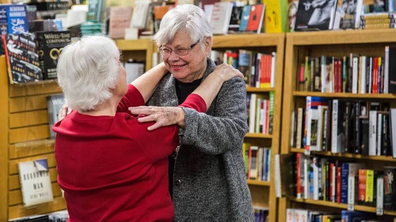 Raleigh writers champion and Quail Ridge Books founder Nancy Olson hugs seasonal gift wrapper, Brenda Holloman, left, in December 2015 at the bookstore in Raleigh.