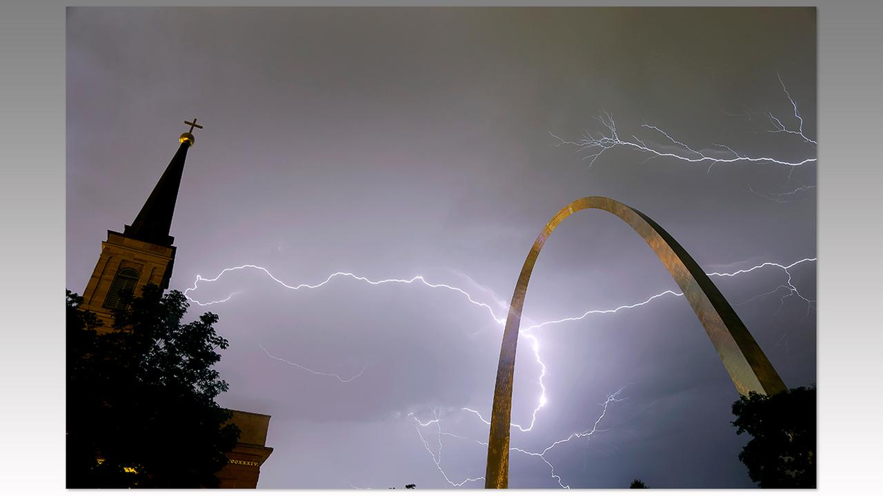 Lightning flashes in the sky behind the Gateway Arch, right, and Old Cathedral, left, as a line of thunderstorms moves through St. Louis, Wednesday, May 11.