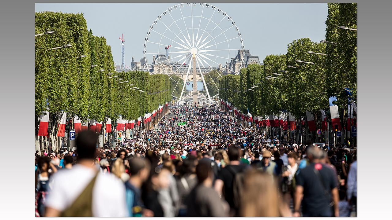 People walk on the Champs Elysees in Paris, Sunday, May 8. Pedestrians have taken over the Champs Elysees as part of a program to ban traffic on the famous avenue once a month.Kamil Zihnioglu