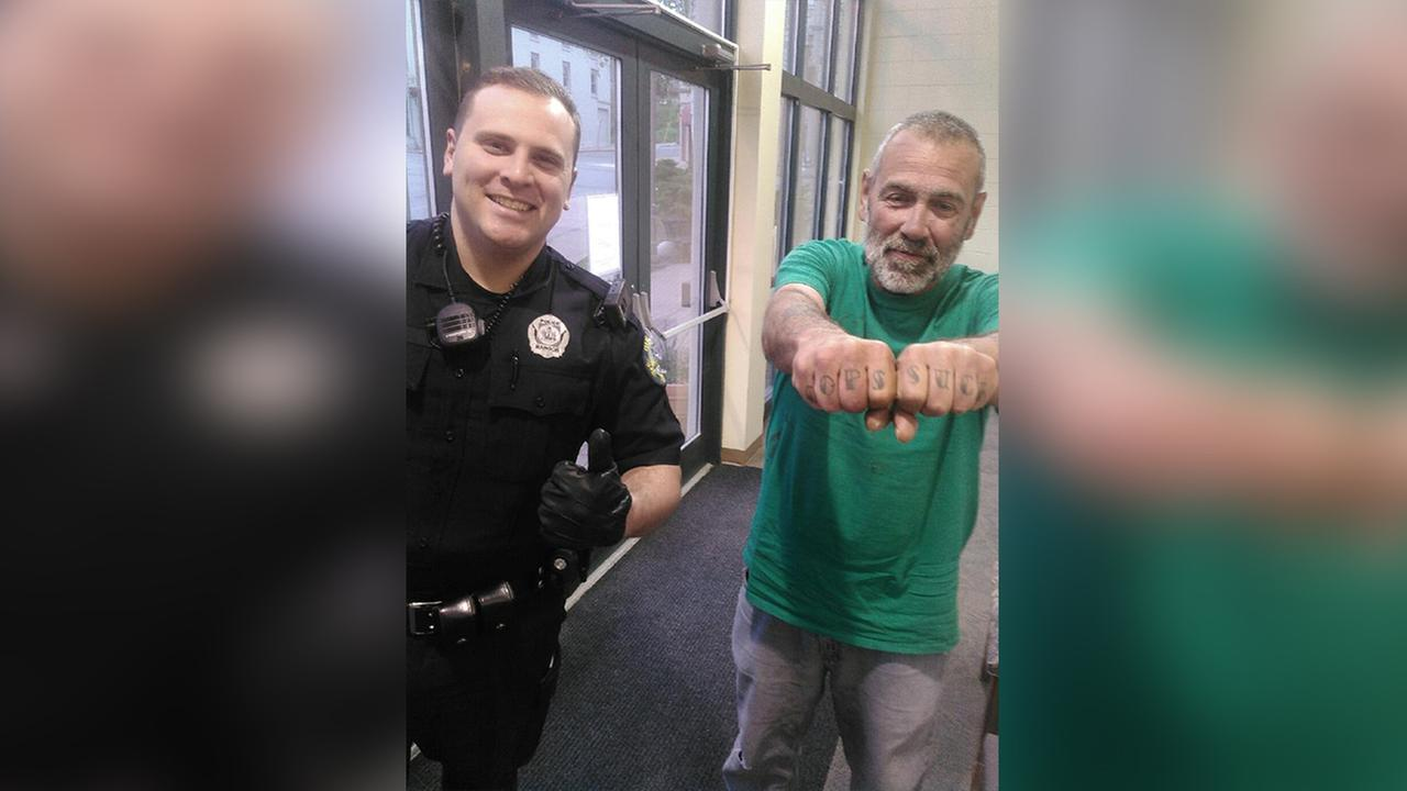 In a Saturday, May 21, 2016 photo provided by the Bangor PD, officer Keith Larby give a thumbs up next to Russell Johnson, who has Cops Suck tattooed on his knuckles