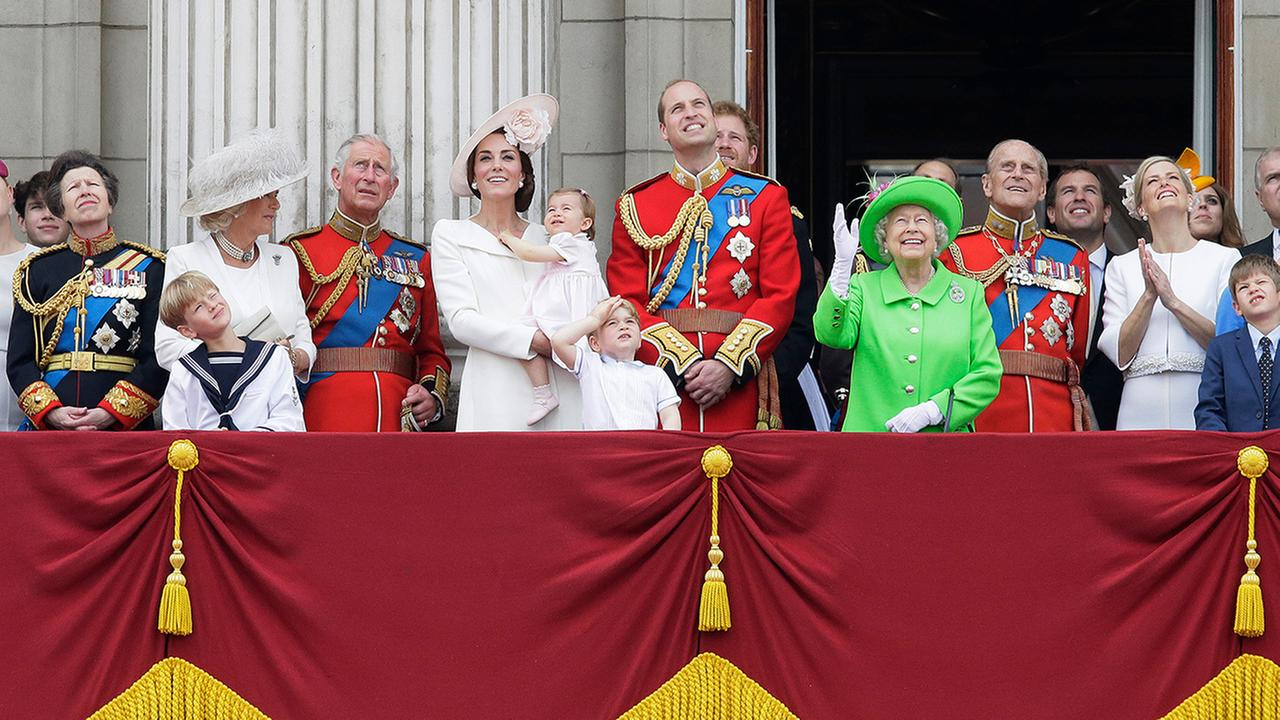 Britains Queen Elizabeth II waves as she watches the flypast, with Prince Philip, Prince William, his son Prince George, and Kate, Duchess of Cambridge holding Princess Charlotte