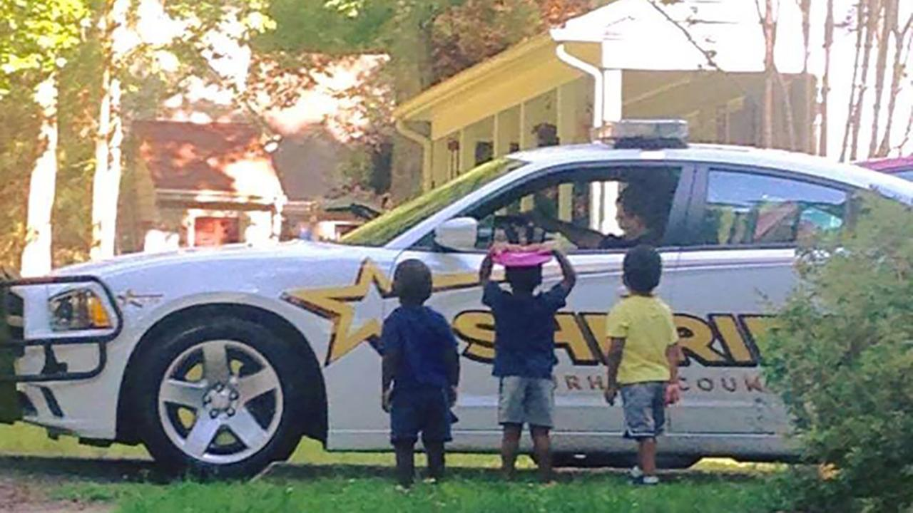 Deputy J. Morgans 3 foster sons greet him after coming home from work