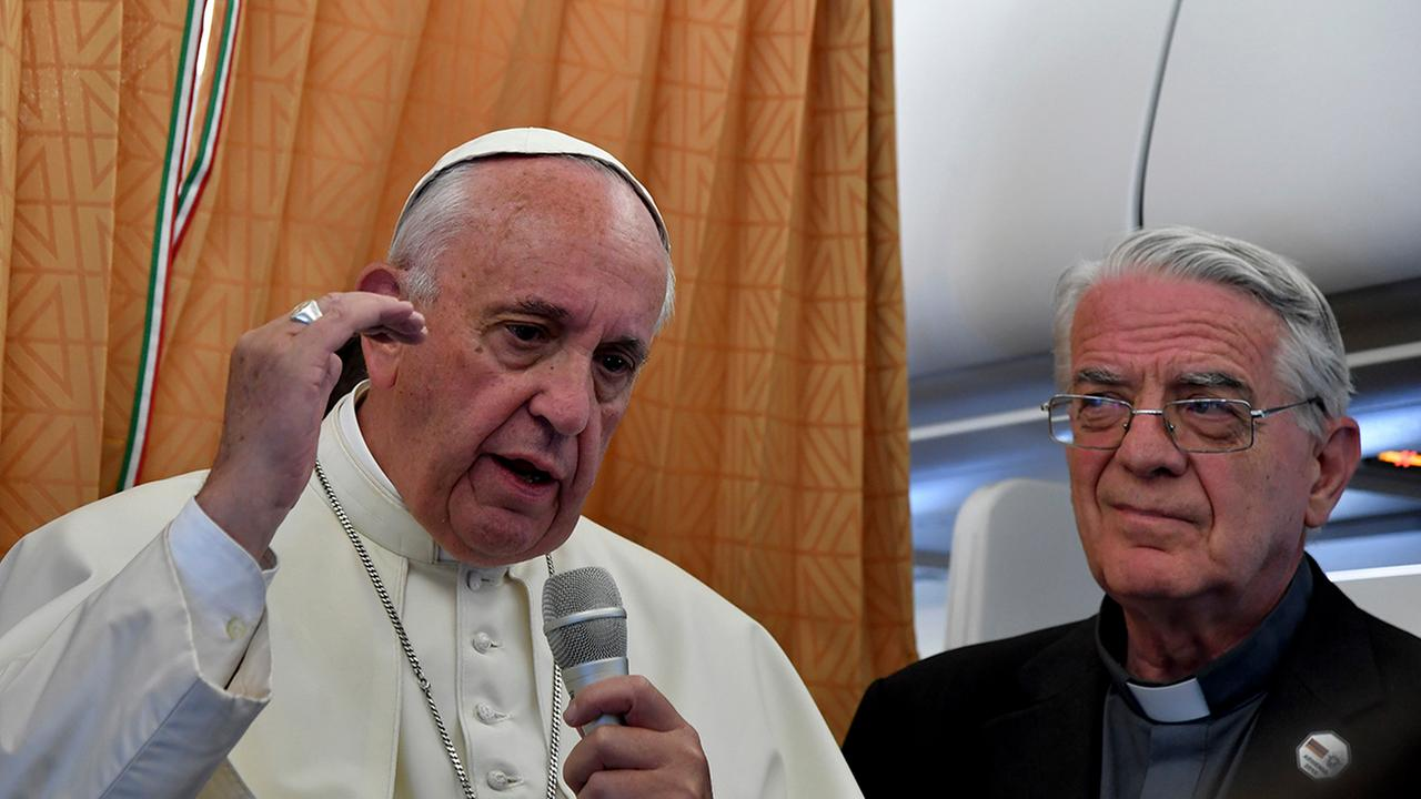 Pope Francis, flanked by Vatican spokesman Federico Lombardi, right, talks to journalists during a press conference he held on board the airplane on his way back to the Vatican