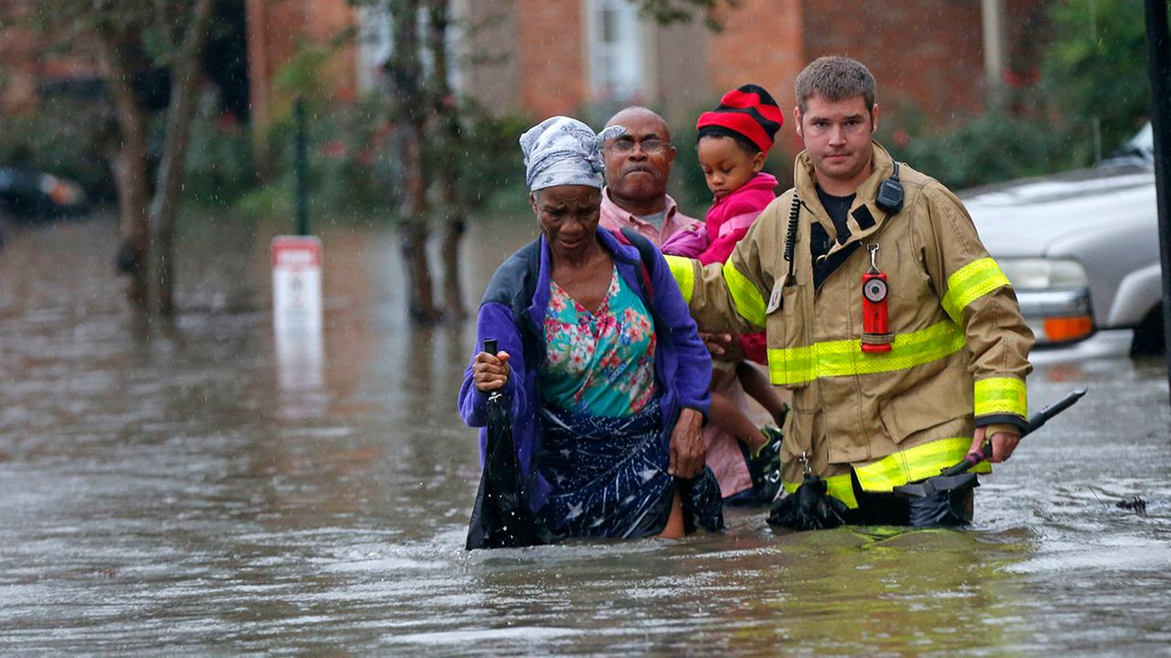 A member of the St. George Fire Department assists residents as they wade through floodwaters from heavy rains in the Chateau Wein Apartments in Baton Rouge, La., Friday, Aug. 12