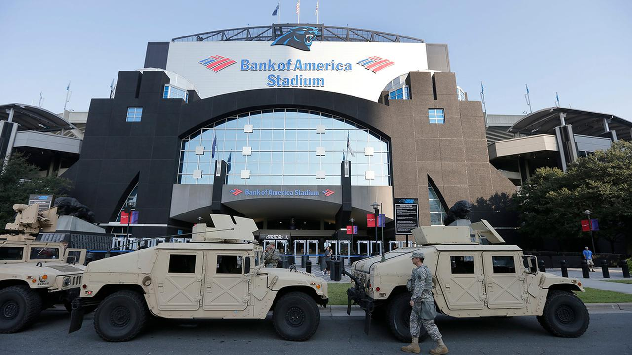 North Carolina National Guard vehicles are parked in front of an entrance to Bank of America Stadium before an NFL football game between the Carolina Panthers and the Minnesota Vikings in Charlotte, N.C., Sunday, Sept. 25, 2016.