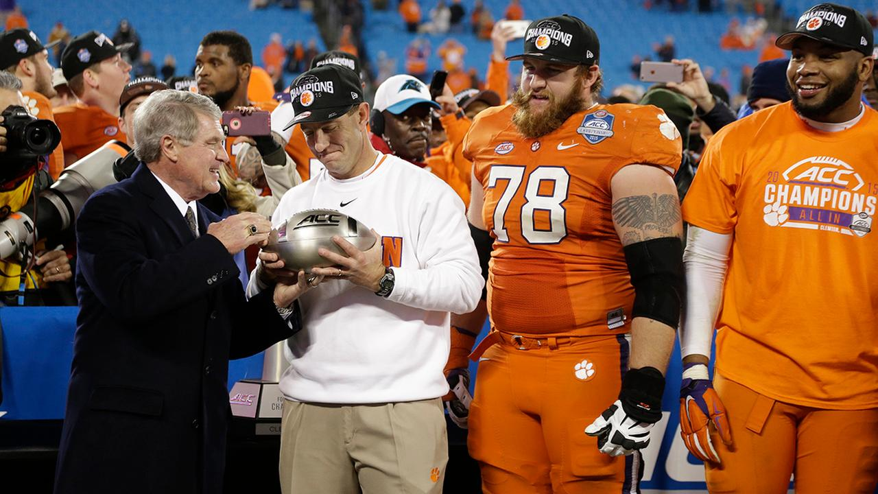 Clemson coach Dabo Swinney accepts the championship trophy from ACC Commissioner John Swofford after Clemson defeated North Carolina in the Atlantic Coast Conference championship