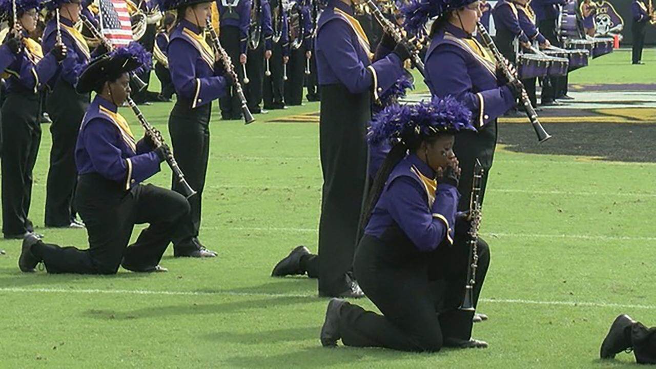 Members of the East Carolina Marching Pirates kneel during the national anthem