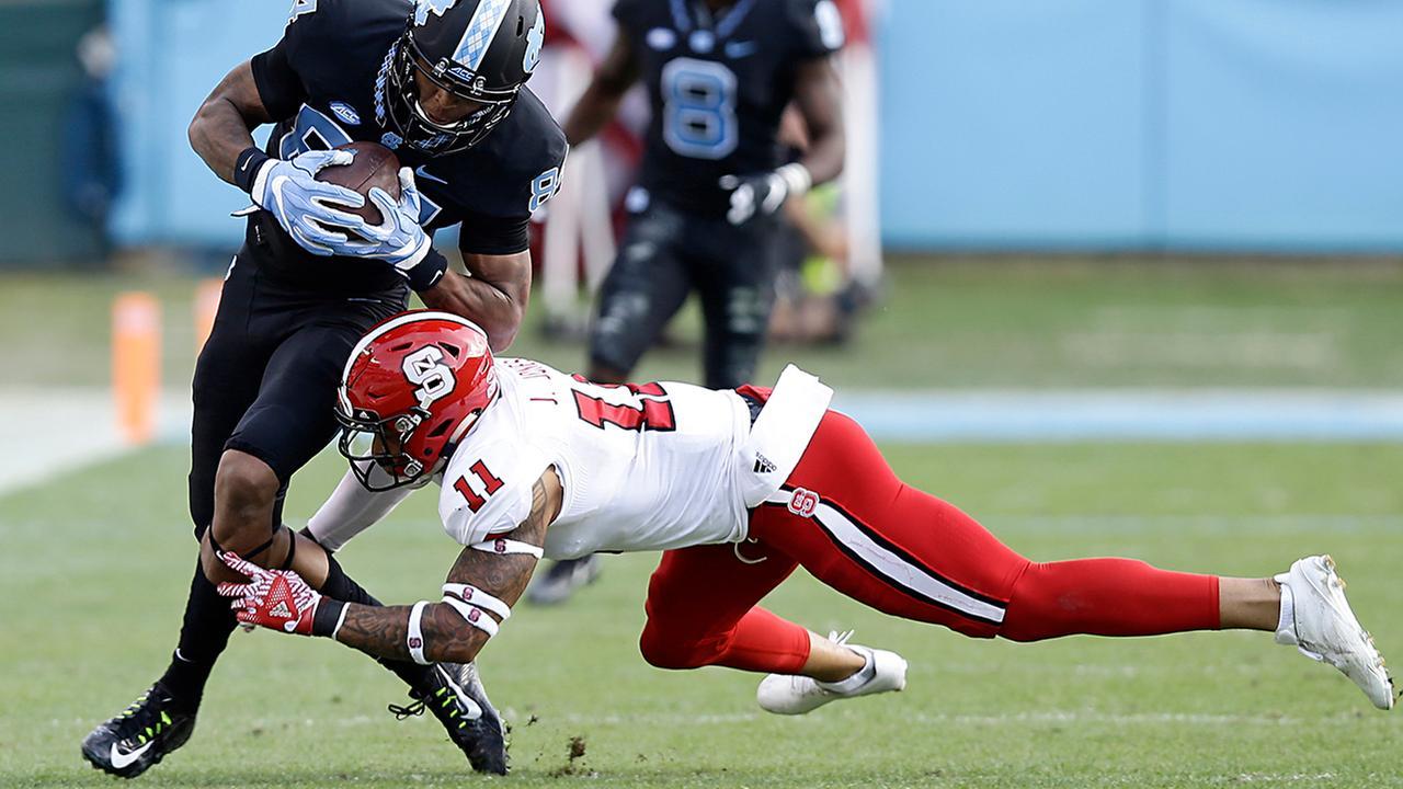 North Carolinas Bug Howard, left, is tackled by North Carolina States Josh Jones.Gerry Broome