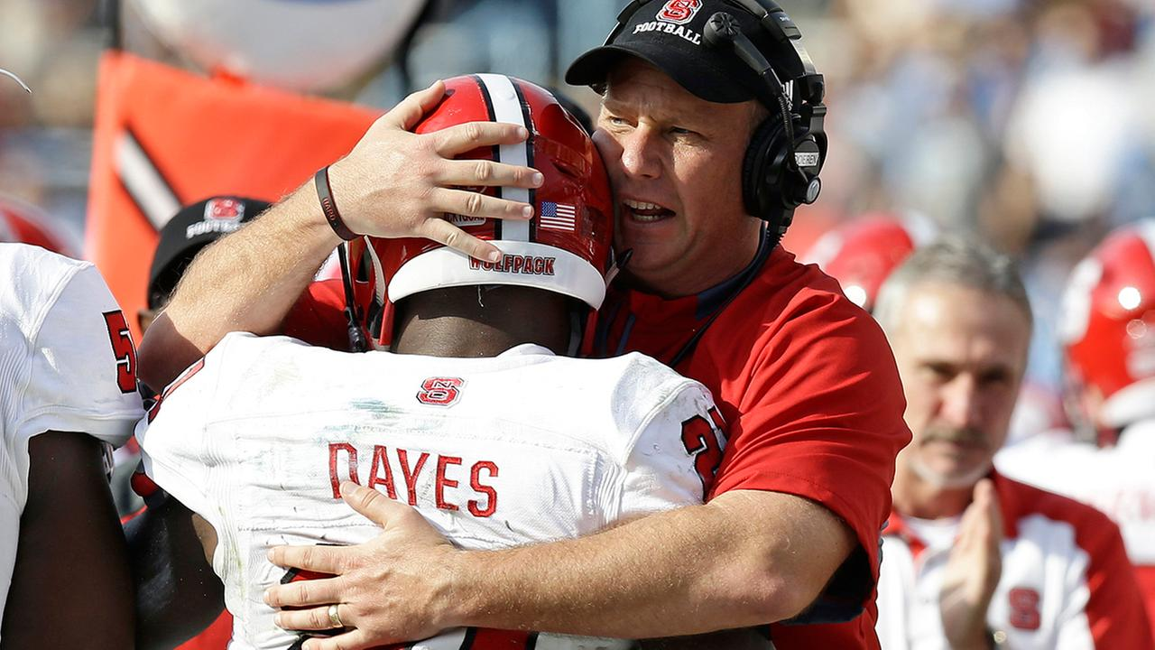 North Carolina State coach Dave Doeren hugs Matt Dayes (21) following Dayes touchdown against North Carolina during the first half.Gerry Broome