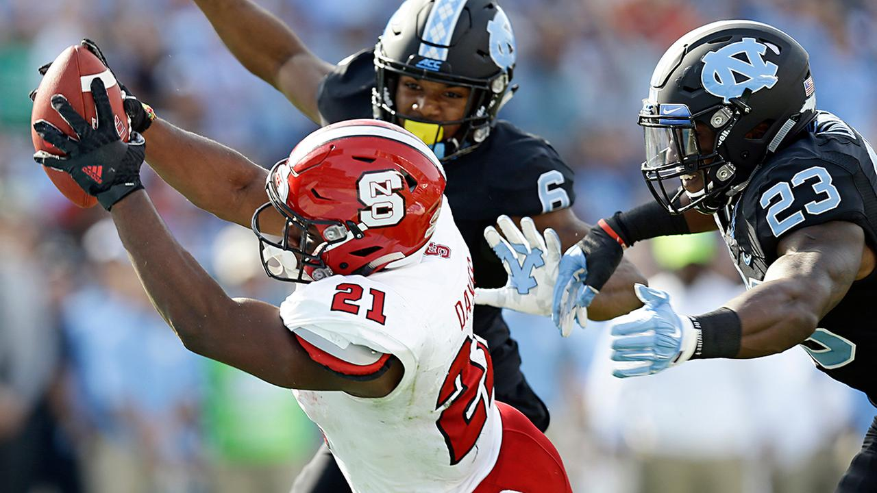 North Carolina States Matthew Dayes (21) reaches out out for a touchdown as North Carolinas M.J. Stewart (6) and Cayson Collins (23) try to tackle on a key fourth-down play.Gerry Broome