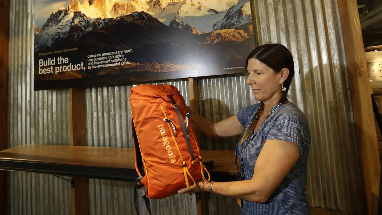 In this July 30, 2013, file photo, Tania Bjornlie, from Patagonia, holds one of the new Patagonia day packs a during set up at the Outdoor Retailer Summer Market in Salt Lake City.