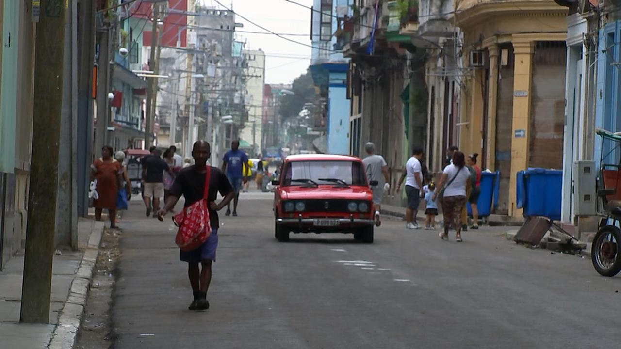 Pedestrians in the streets of Havana make way for a car.Adolfo Ibarra
