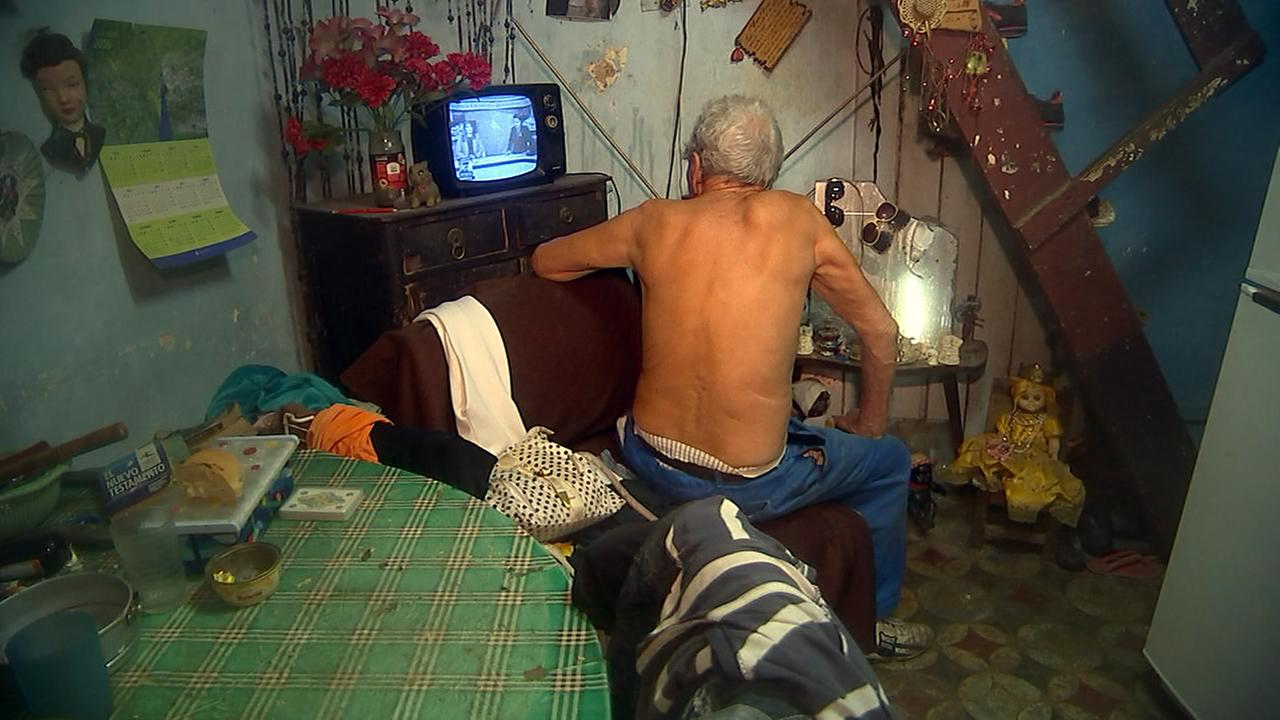 A man watches the local news coverage of Fidel Castros funeral procession.Adolfo Ibarra
