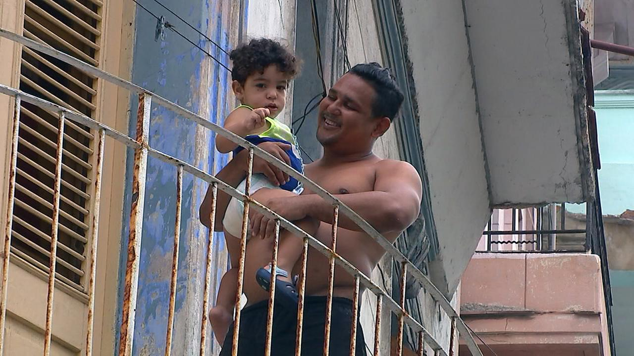 A dad and his son wave to the camera.Adolfo Ibarra