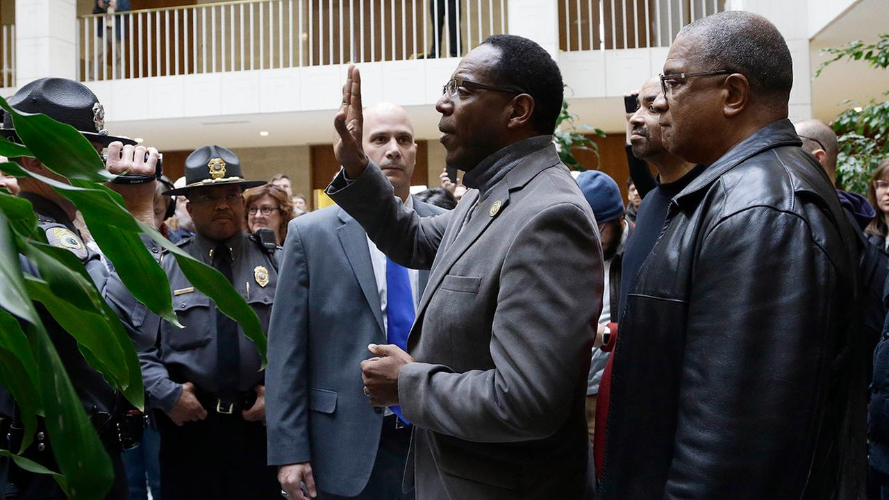 Rev. Curtis Gatewood, with the North Carolina chapter of the NAACP raises a hand as he is confronted by General Assembly police at a demonstration.Gerry Broome
