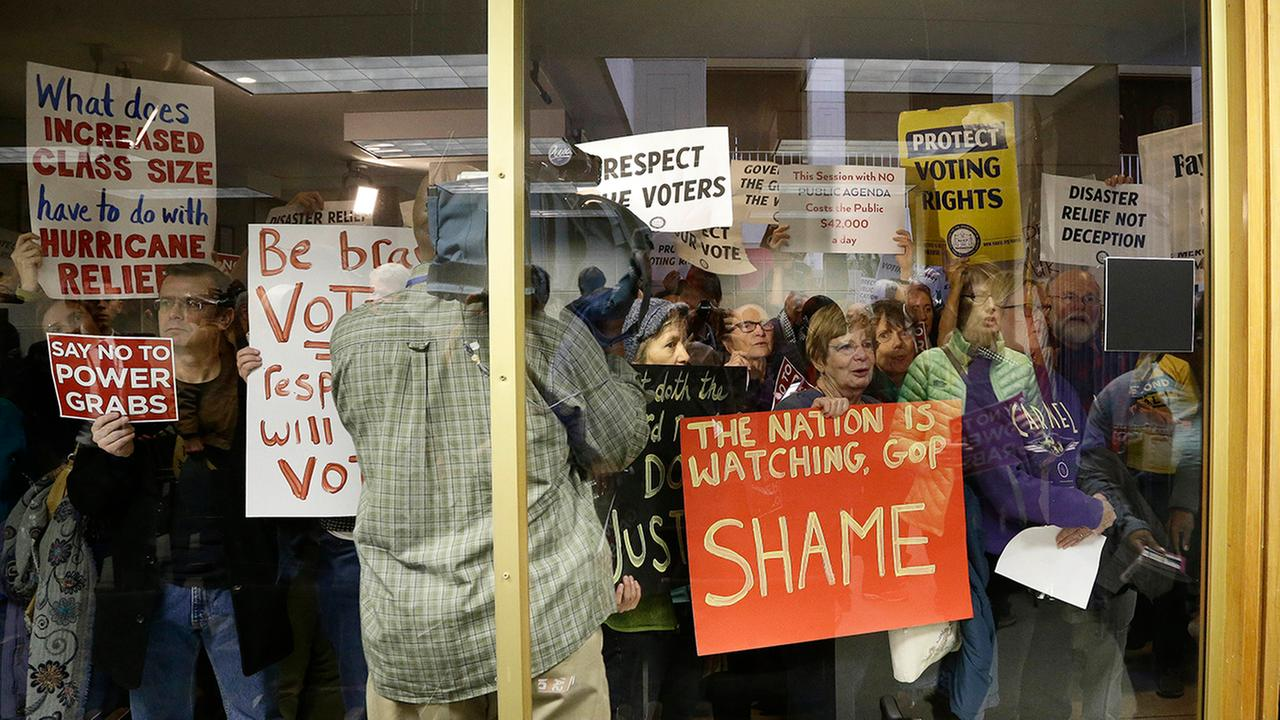 Protestors gather outside of a press conference room during a special session Thursday.Gerry Broome
