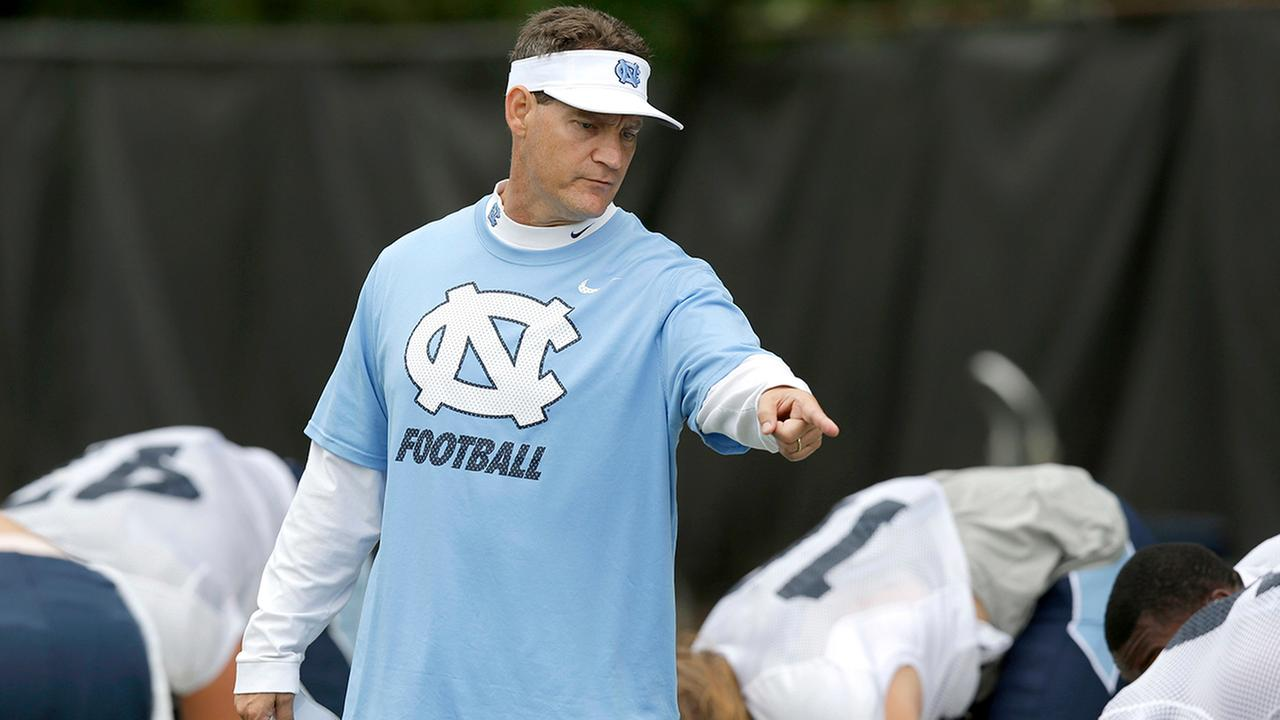 FILE - In this Aug. 10, 2015, file photo, North Carolina defensive coordinator Gene Chizik works with players during an NCAA college football practice in Chapel Hill, N.C.