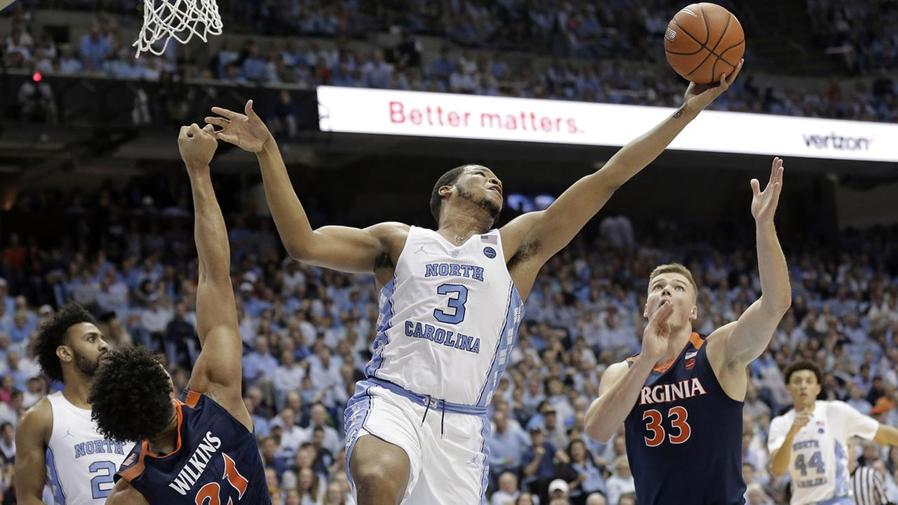 North Carolinas Kennedy Meeks (3) reaches over Virginias Isaiah Wilkins (21) and Jack Salt (33)  (AP Photo/Gerry Broome)