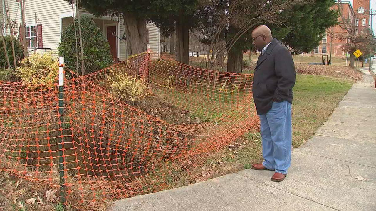 Thomas Parrish shows Diane Wilson the sinkhole in his Durham neighborhood