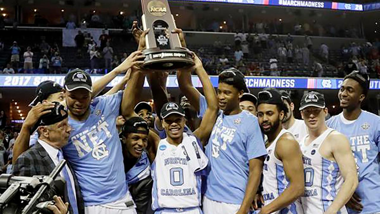 North Carolina players and coaches celebrate after beating Kentucky 75-73 in the South Regional final game