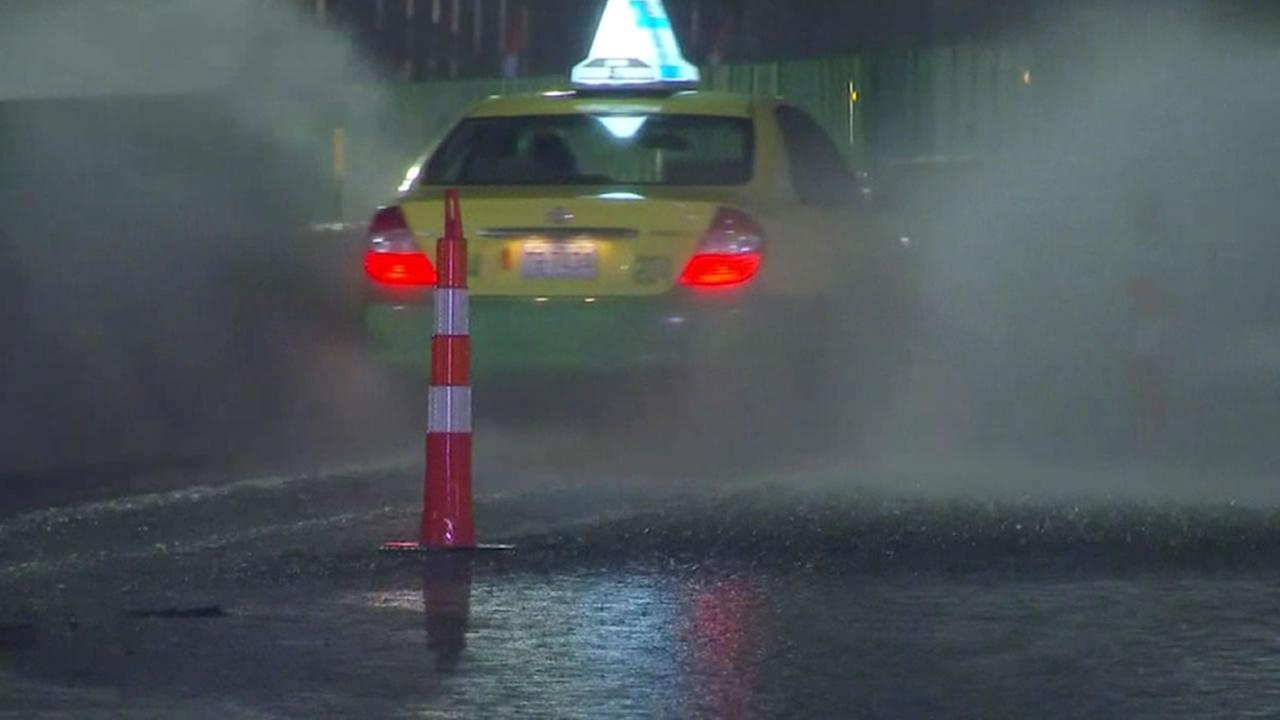 A taxi negotiates water on the road in Raleigh