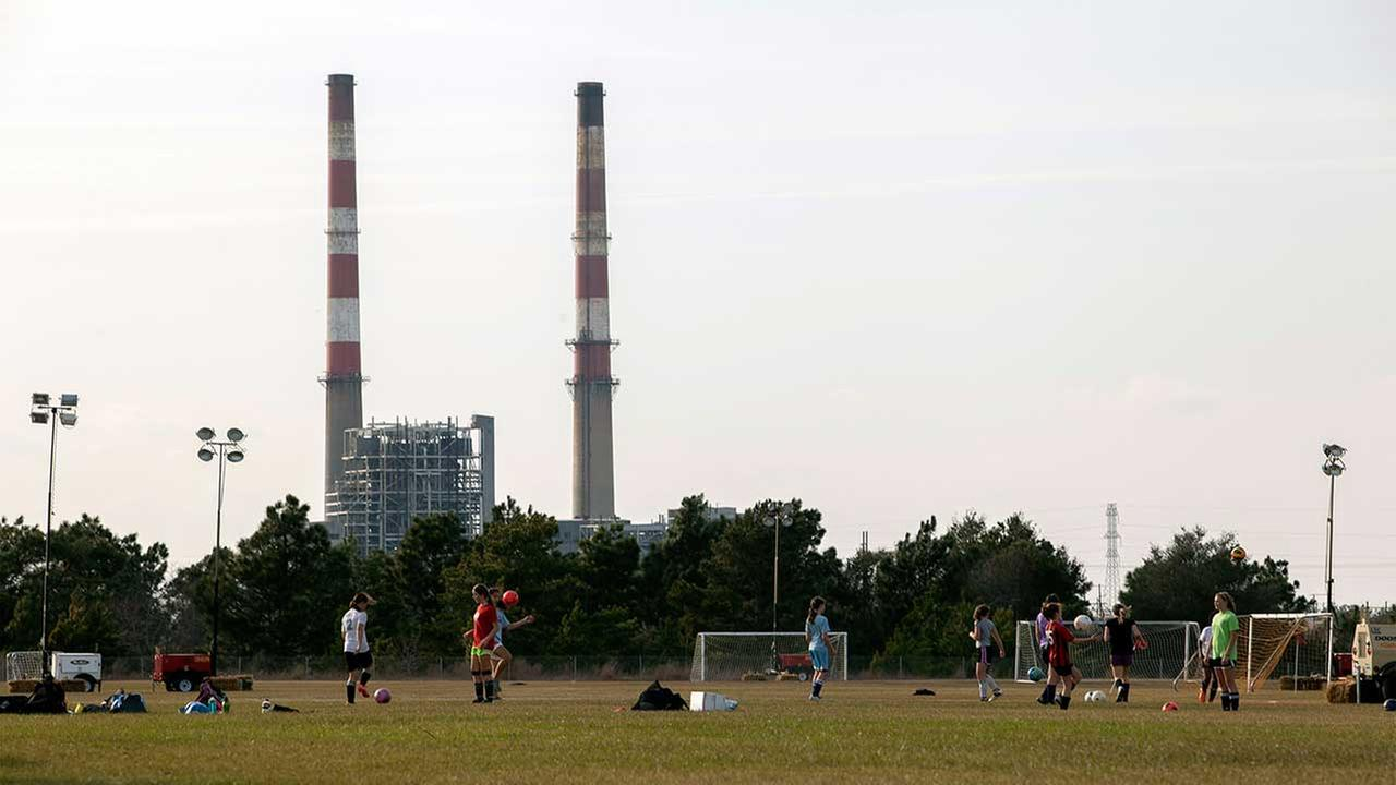 In this Feb. 19, 2014 file photo, girls play on a soccer field near the L.V. Sutton Complex operated by Duke Energy in Wilmington, N.C.