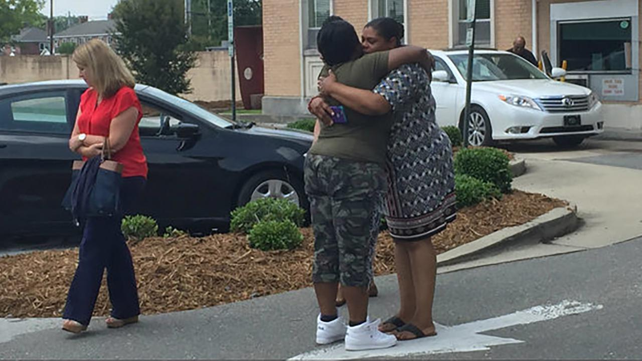 Family members of homicide victim Donald Girtley Jr. embrace after a Kinston Police Department press conference on Thursday, June 1