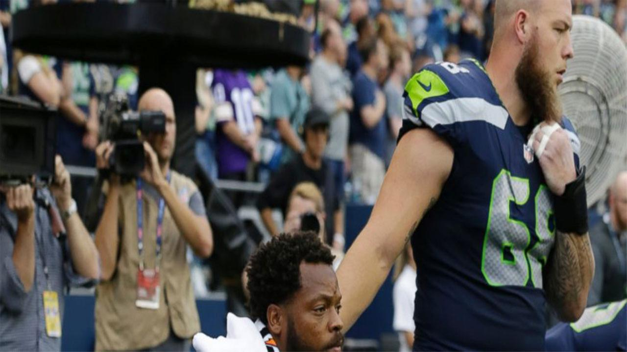 Seattle Seahawks center Justin Britt, right, stands next to defensive end Michael Bennett as Bennett sits on the bench